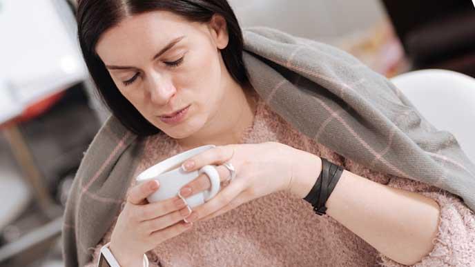 肩までブランケットをかけてコーヒーを飲む女性社員