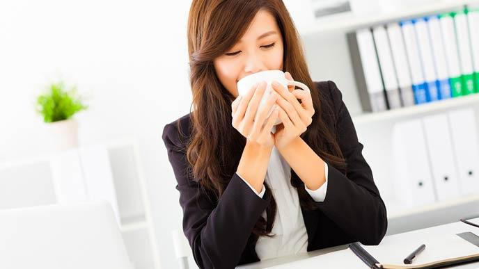 ホットコーヒーを飲む女性事務員
