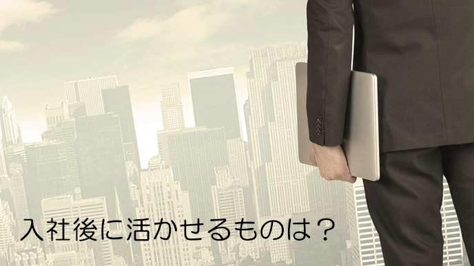 ラップトップを持ってビジネス街を見つめるビジネスマン