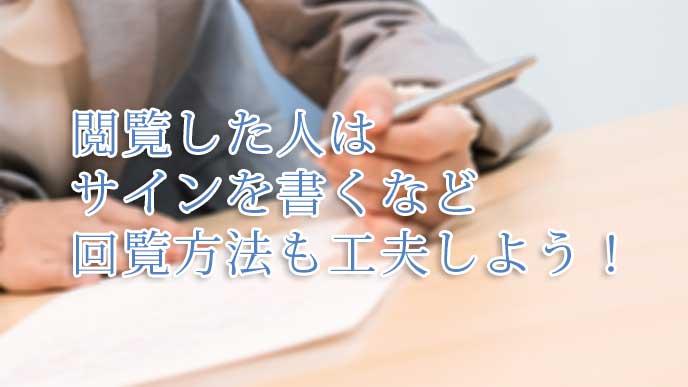 社内文書を閲覧し終わったことを記すサインをしてるスーツを着た女性