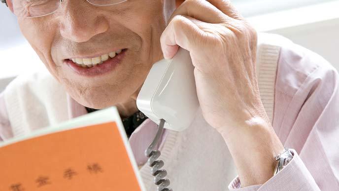 年金手帳を見ながら電話で問い合わせる年配の男性
