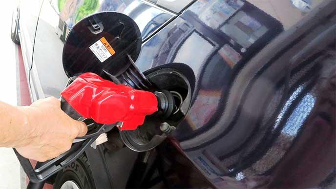 ガソリンスタンドで車に給油してる男性スタッフ