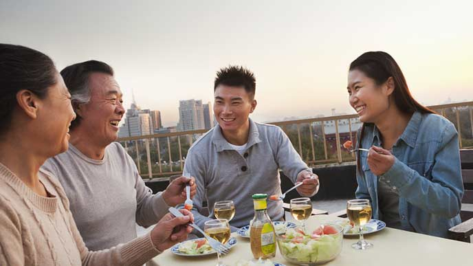 親と一緒にテラスで食事する若夫婦