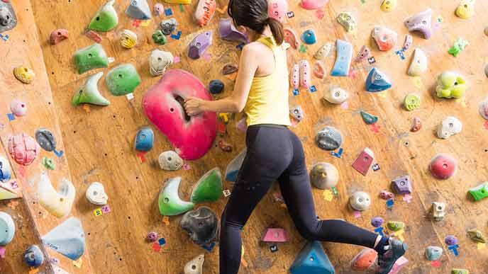 ボルダリングジムで壁を上る女性