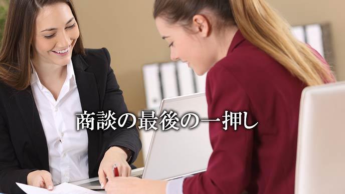 女性営業マンがお客に契約書のサインをさせる