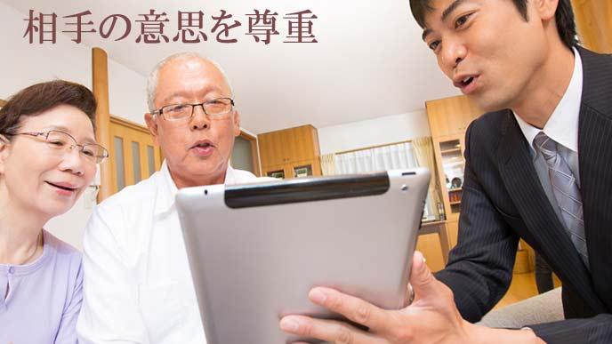 年寄り夫婦に説明する営業マン