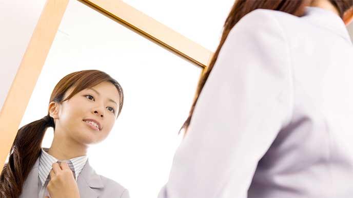 鏡を見ながら身だしなみを整えてる女性社員
