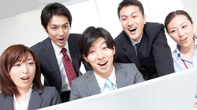 みんなで一緒のパソコンを見て驚いているビジネスマンたち