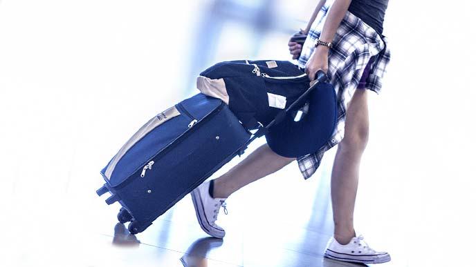 空港ロビーをキャリーバッグを引いて歩く若者