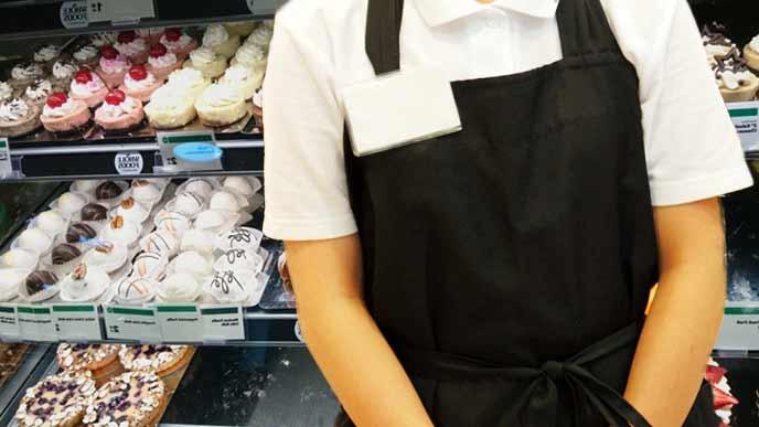 ケーキのショーケースの前に立つアルバイト店員