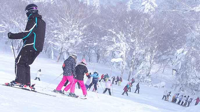 ゲレンデでスキーする人々