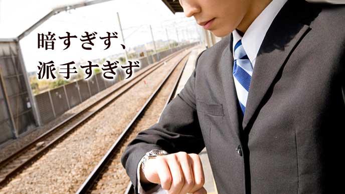 ホームで電車を待つスーツ姿の男性