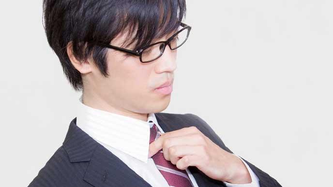 ネクタイを締めなおす社員