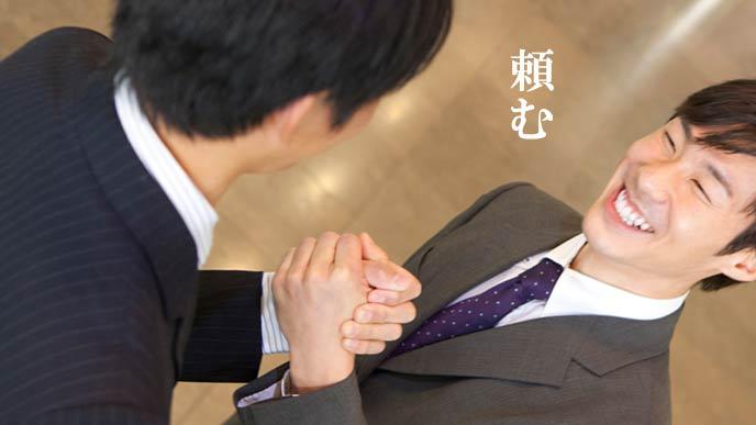 手を組み合わせる二人の男性