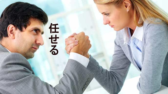男性の上司と腕相撲する部下の女性