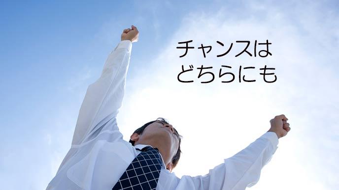 青空に向かって両腕を広げる男性
