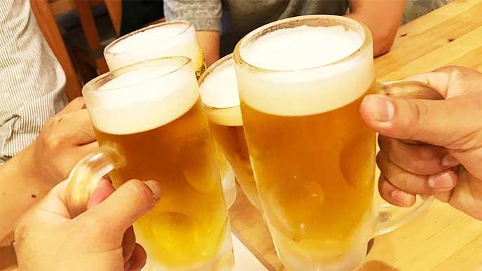 居酒屋でビールで乾杯してる人たち