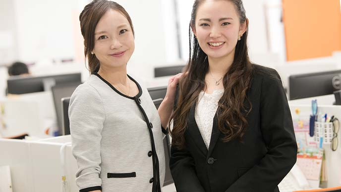 事務所内で新人を迎える女性社員