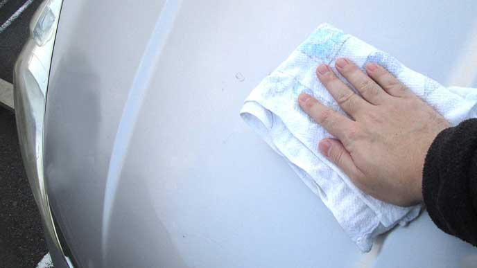 車のボンネットを雑巾で拭く