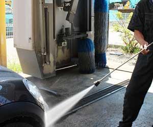 高圧水で洗車する男性