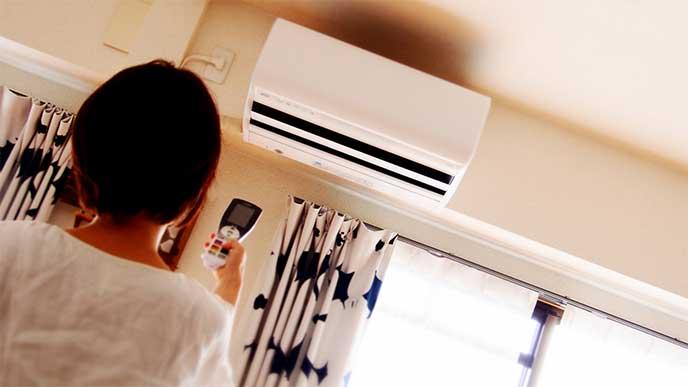 リモコンでエアコンのスイッチを入れてる女性