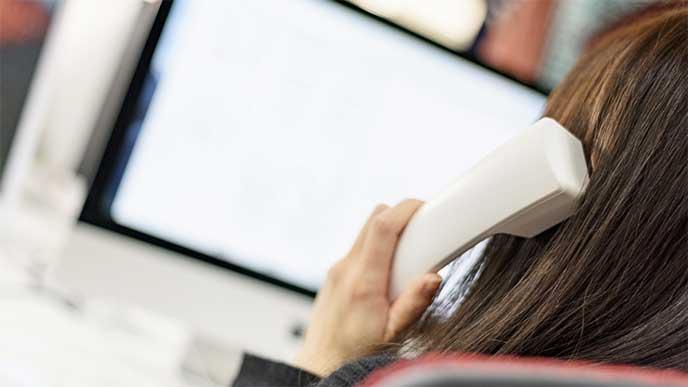 パソコンの前に座って電話をし仕事をしてる女性
