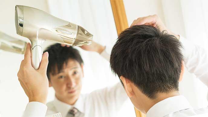 朝仕事に行くためにドライヤーを使ってヘアセットしてる男性