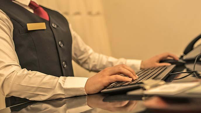 漫画喫茶でパソコンを操作して受付業務をする女性