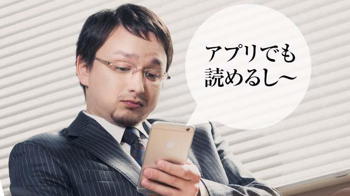 スマートフォンアプリでニュースを読む会社員