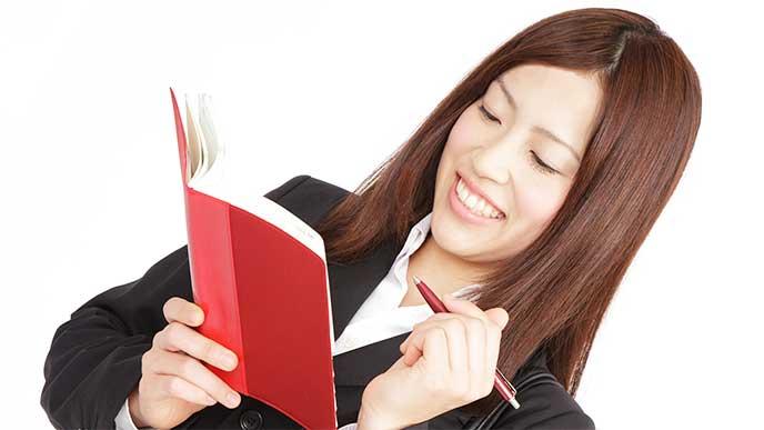 就活日記をつけてるリクルートスーツを着た女性