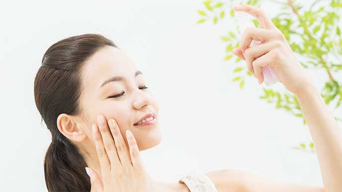 ミスト化粧水を顔に吹きかけてる女性
