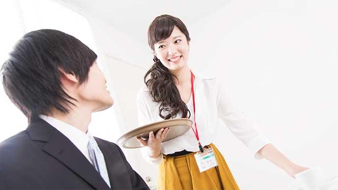 男性社員にお茶を出す笑顔んの女性