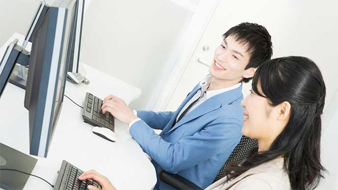 メンターと並んでパソコンを操作してる新入社員