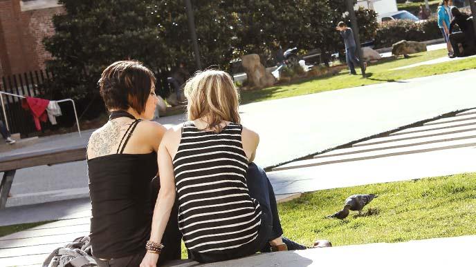 海外の大学ですわりこんで話しをする女性二人