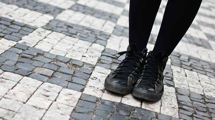 黒のスニーカーを履いて路上に立つ