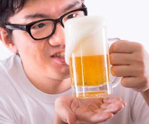 グラスの中のビールを見つめる男性