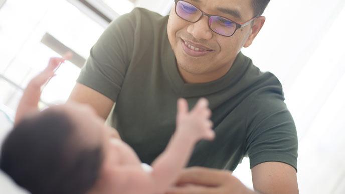 赤ちゃんのオムツを替える父親