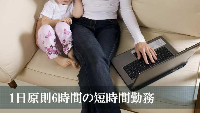幼児を隣に座らせてパソコンを操作する母親