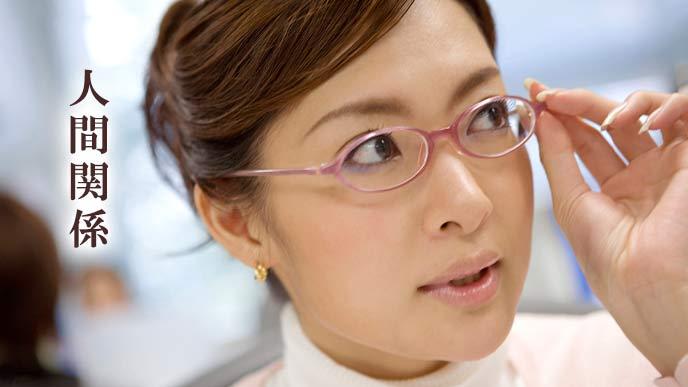 眼鏡を指で押さえながら同僚を注視する女性社員