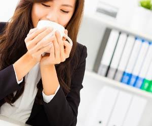 デスクでお茶を飲む女性社員