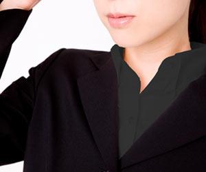 黒いスーツと黒いシャツの女性