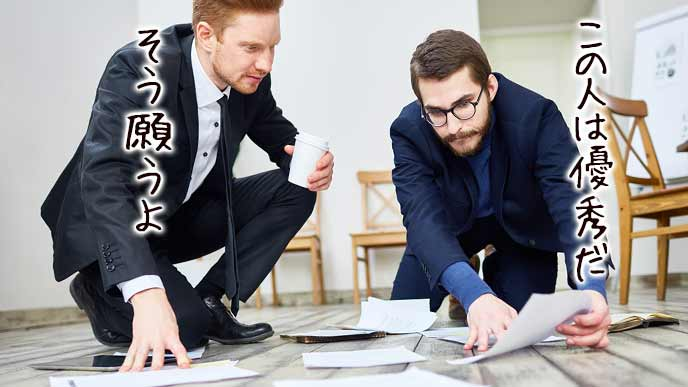 床に広げた応募書類を見ながら話し合う社員