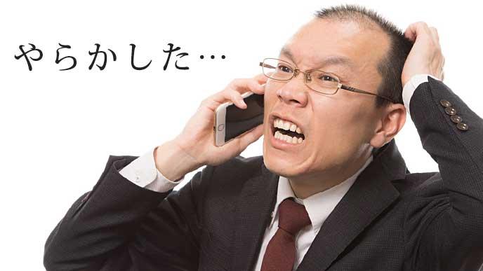 電話を片手に頭を抑えるサラリーマン