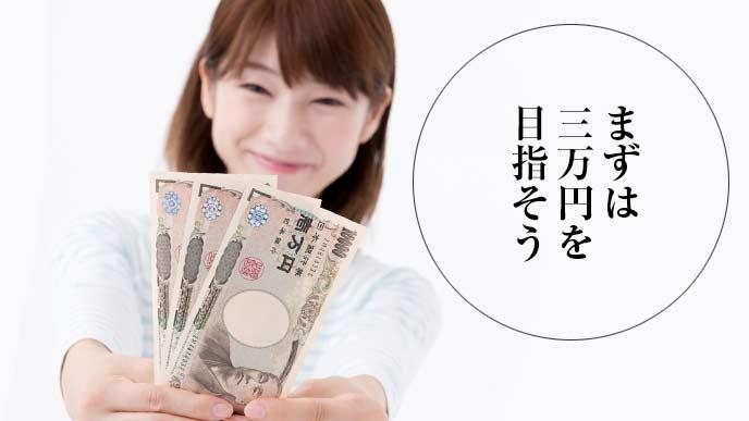 3万円をもってアピールする女性