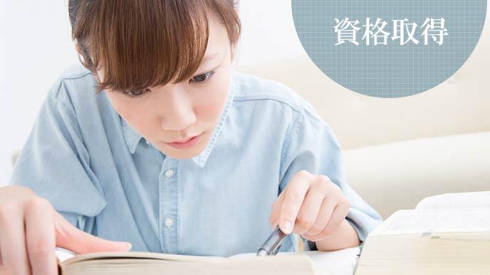 テキストを読みながら勉強する女性