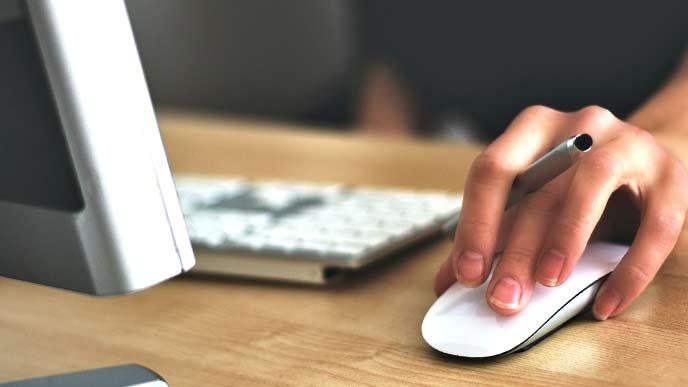 マウスを操作しながら仕事をしている男性