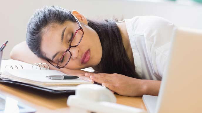 窓際で昼寝をしている会社員女性