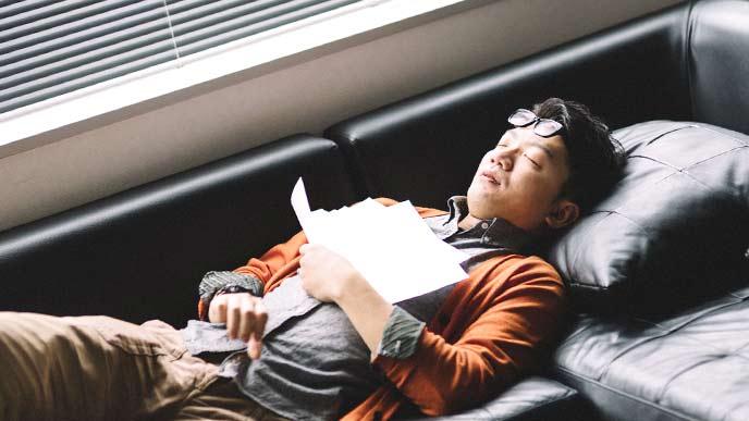 ソファーの上で眠る男性会社員