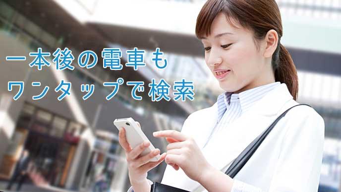 駅でスマホアプリを使っている会社員の女性