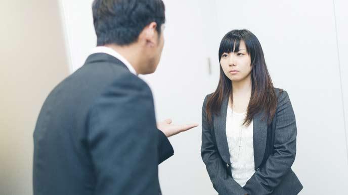 女性社員と男性上司が廊下で会話をしている